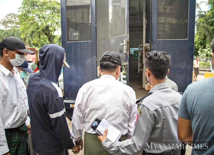 Corruption suspects are escorted to a police vehicle. The Anti-Corruption Commission is looking to hire more personnel. The Myanmar Times