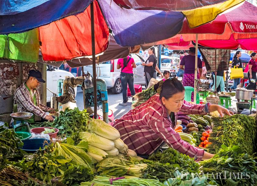 A woman arranges vegetables for sale at a market in Yangon. Government statistics show that inflation peaked last December. Nyan Zay Htet/The Myanmar Times