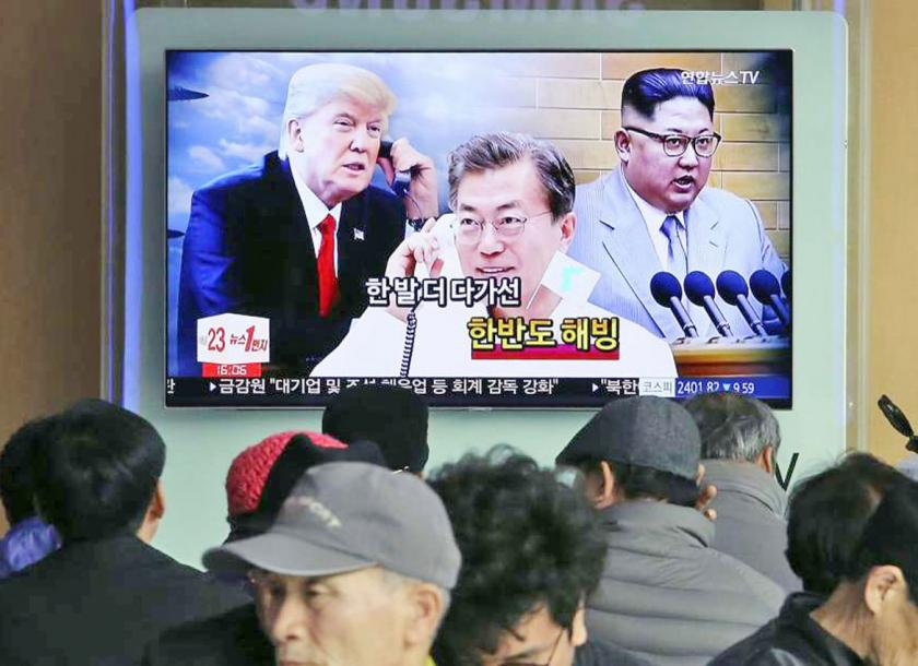 People watch a TV screen showing North Korean leader Kim Jong Un right South Korean President Moon Jae-in centre and US President Donald Trump at the railway station in Seoul South Korea on March 7