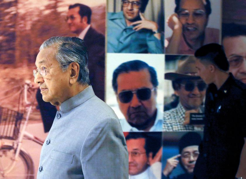 New Malaysian Prime Minister Mahathir Mohamad walks by a board displaying his