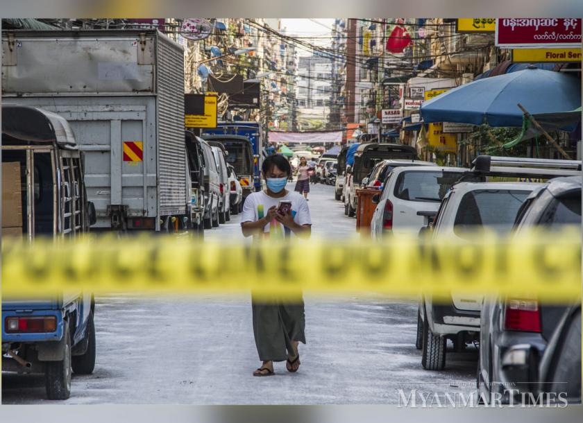 A man wearing a face mask checks his phone on a street under lock down in Yangon. Photo: Mar Naw/The Myanmar Times