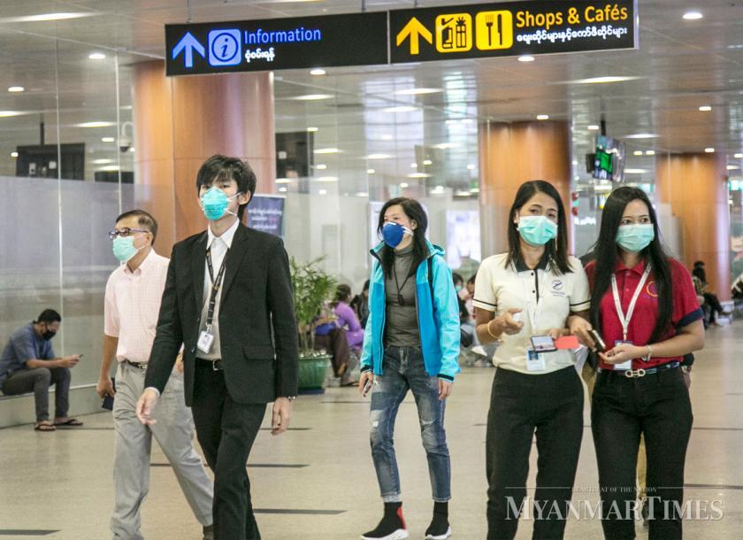 People wear face masks at Yangon International Airport. Theint Mon Soe (J)/The Myanmar Times