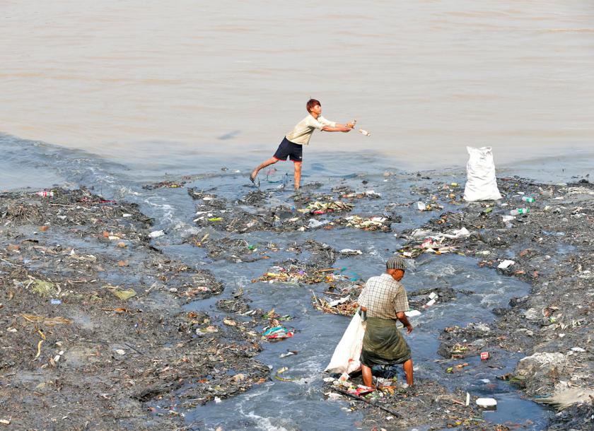 People collect recyclable materials on the banks of the Yangon River in Yangon. Photo - EPA