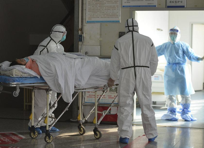 Medical workers in protective suits move a coronavirus patient into an isolation ward at the Second People's Hospital in Fuyang in central China's Anhui Province on Saturday. Photo: AP