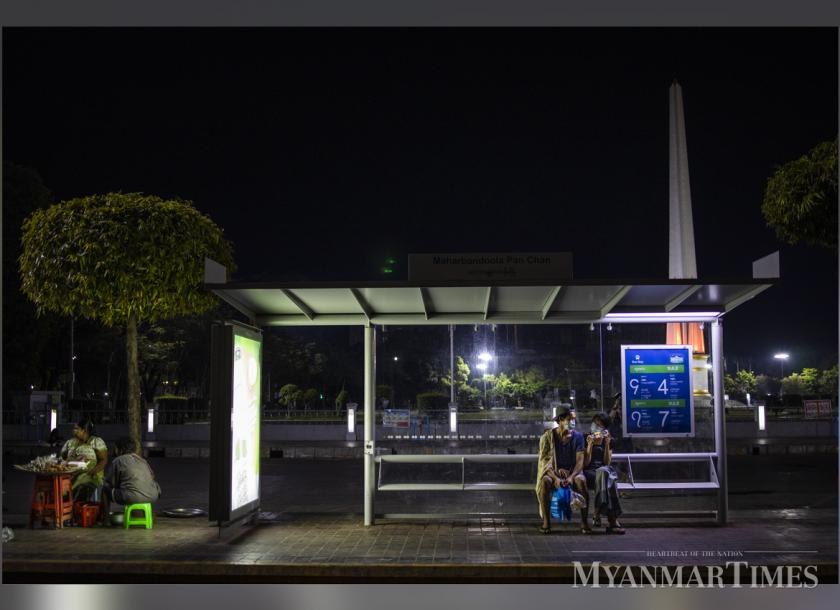 Commuters seen waiting for a bus at the Mahabandula Park stop in downtown Yangon. Photo: Nyan Zay Htet/The Myanmar Times