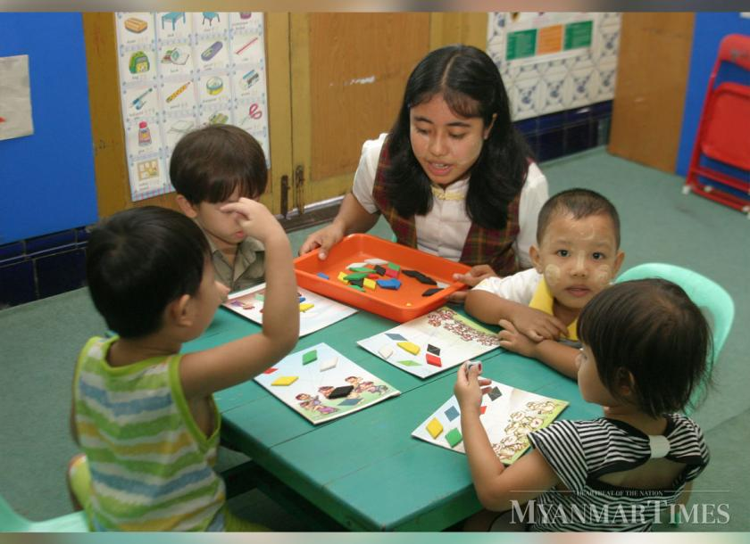 A pre-school employee plays games together with the students in Yangon. Photo: Myanmar Times