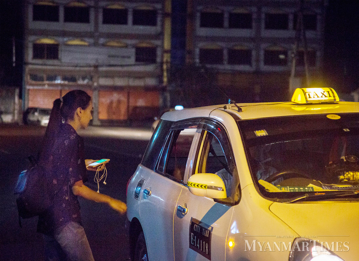 A passenger stops a cab ordered on the Grab app. Nyan Zay Htet/The Myanmar Times